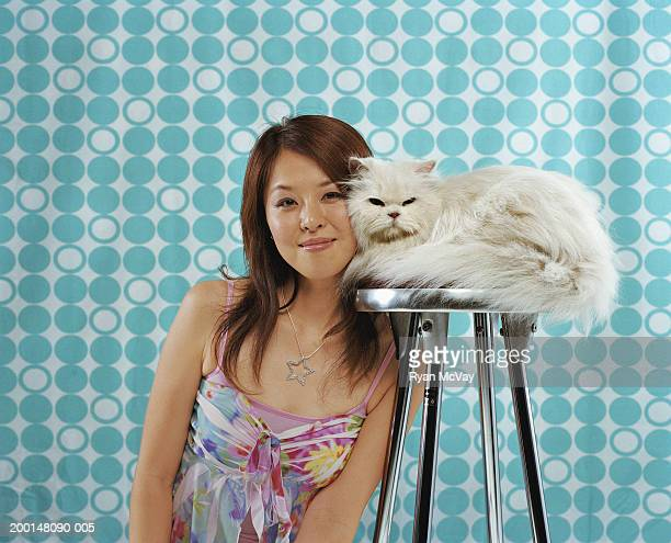 Young woman sitting next to Persian cat