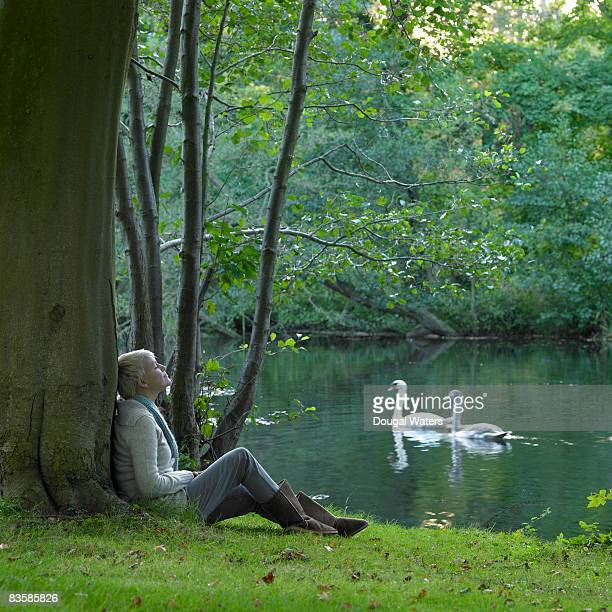 Young woman sitting next to river against tree.