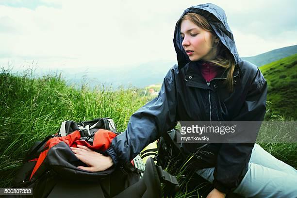 Junge Frau sitzt auf einem Rucksack in Bergen.