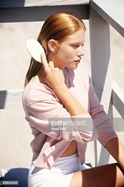 young woman sitting on a balcony, brushing her hair - menselijk haar stockfoto's en -beelden