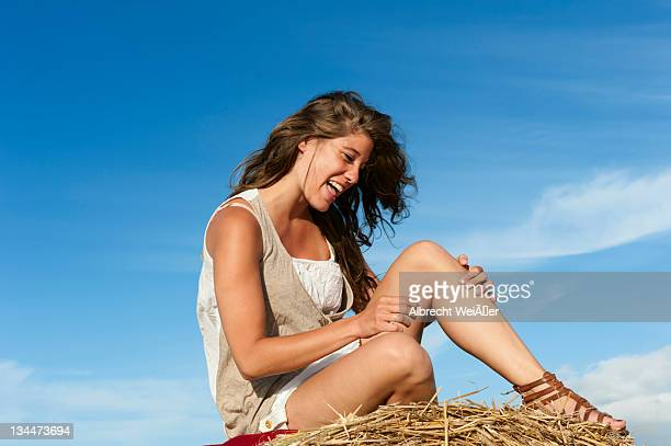 young woman sitting on a bale of straw - vista lateral stock pictures, royalty-free photos & images