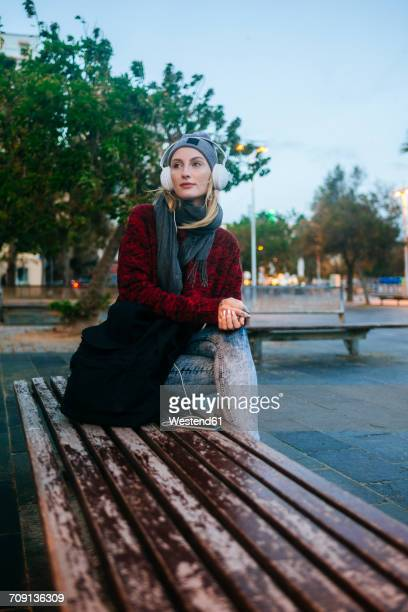 Young woman sitting on a bench listening to music