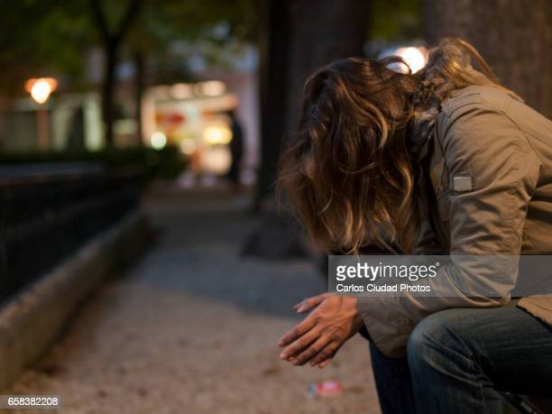 young woman sitting on a bench looking down at night - suicide stock photos and pictures