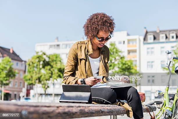 Young woman sitting on a bench reading notes