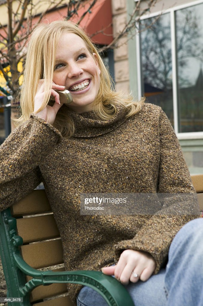 Young woman sitting on a bench using a mobile phone : Foto de stock