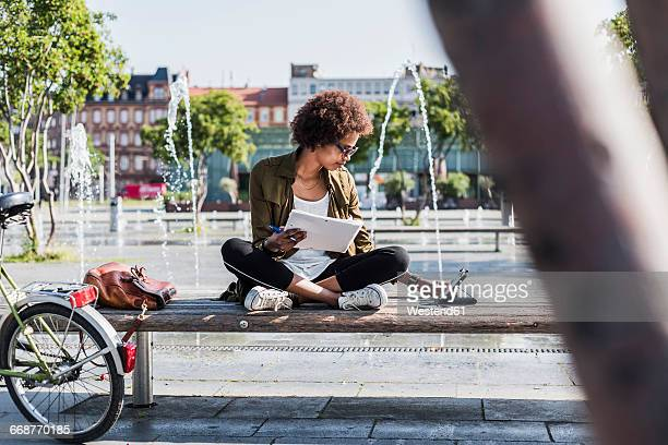 Young woman sitting on a bench with notebbok looking at digital tablet