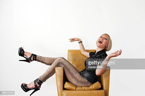 young woman sitting on a chair, laughing - leather shirt stock pictures, royalty-free photos & images
