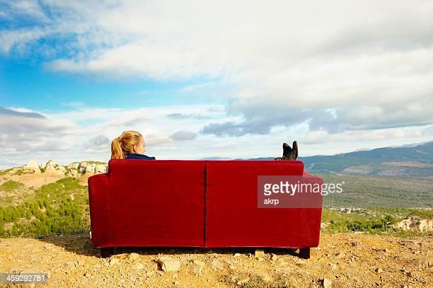 Jeune femme assise sur un canapé à l'extérieur