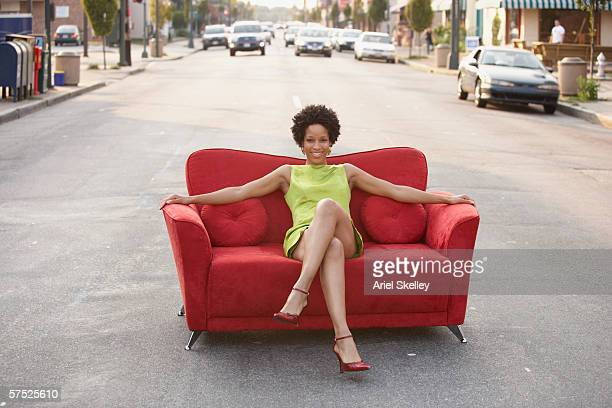 Young woman sitting on a couch outdoors