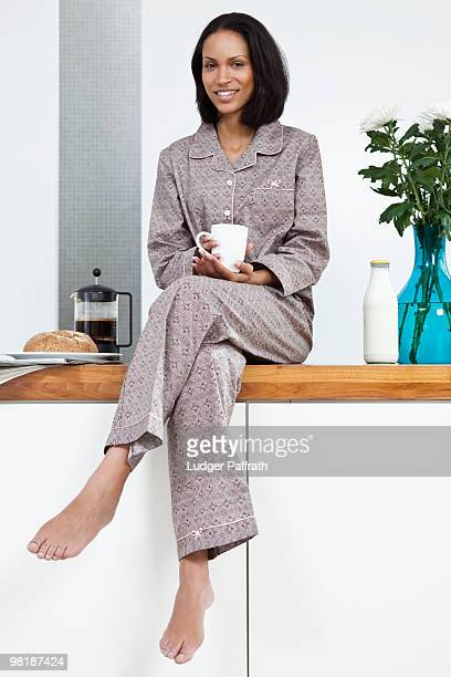 A young woman sitting on a kitchen counter, breakfast