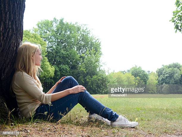 Young woman sitting on a meadow leaning on tree trunk
