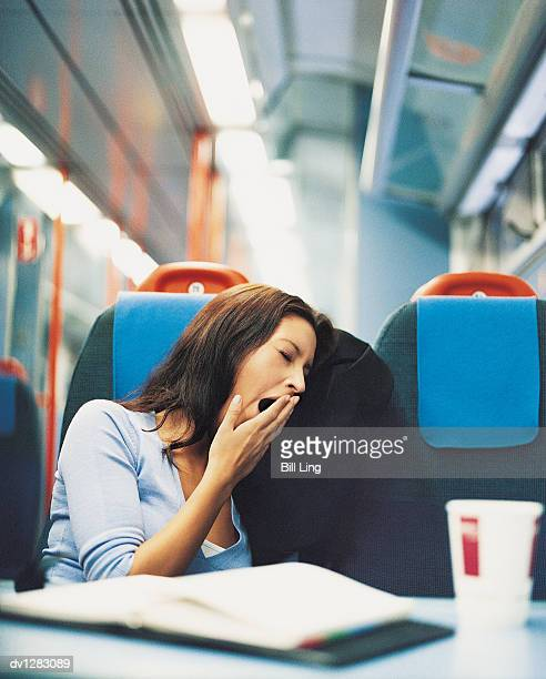 Young Woman Sitting on a Passenger Train and Yawning
