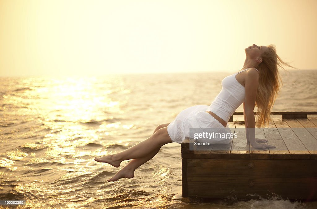 Young woman sitting on a pier enjoying life at sunset : Stock Photo