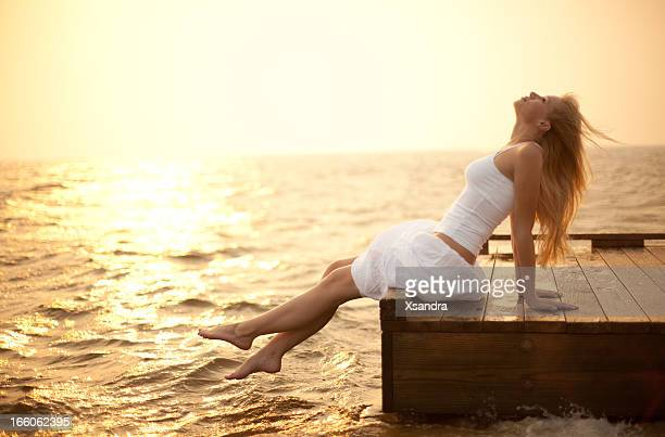 Young woman sitting on a pier enjoying life at sunset