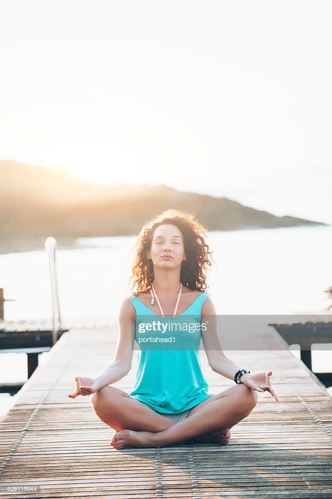 Jeune femme assis sur un quai en posture de lotus : Photo