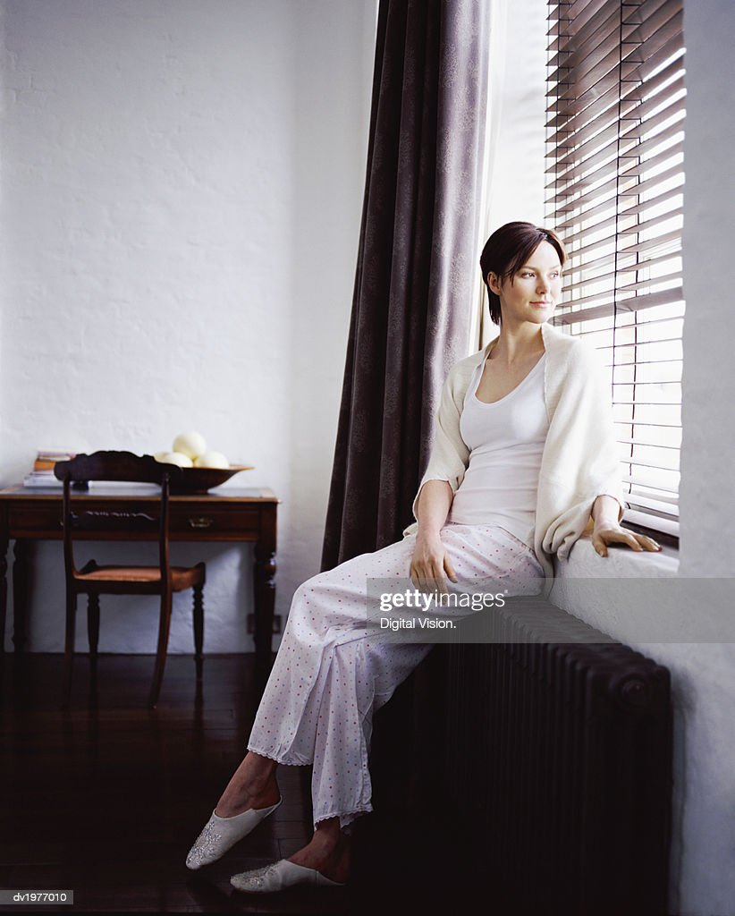 Young Woman Sitting on a Radiator Looking Out of a Window in a Home Showcase Interior : Stock Photo