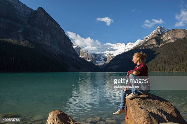 Young woman sitting on a rock by the lake relaxing