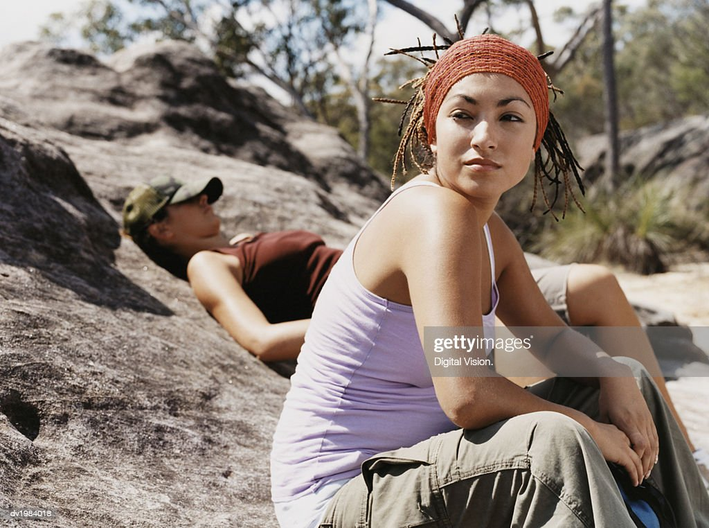Young Woman Sitting on a Rock With Another Woman Lying in the Background : Stock Photo