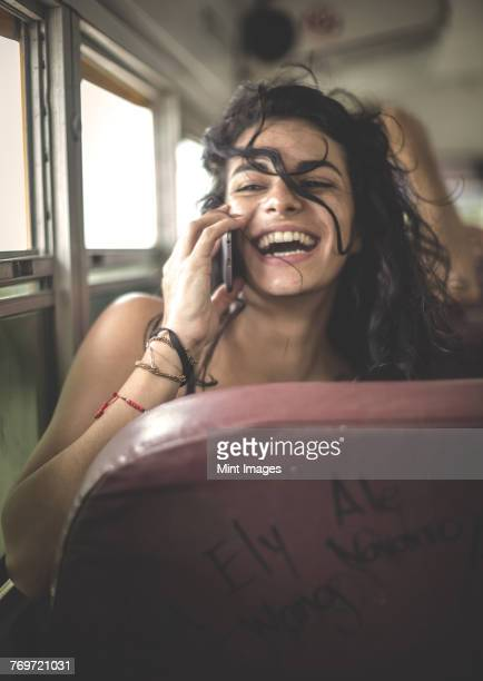 Young woman sitting on a school bus holding a mobile phone to her ear.