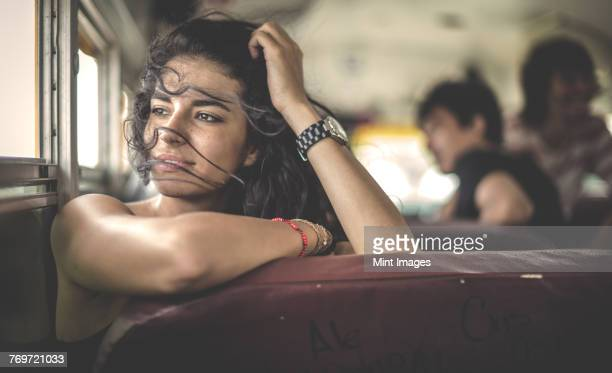 A young woman sitting on a school bus looking out of window.