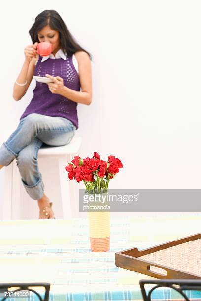 Young woman sitting on a stool and drinking tea