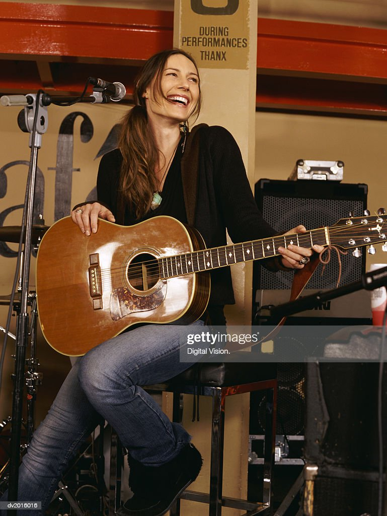 Young Woman Sitting on a Stool and Holding an Acoustic Guitar : Stock Photo