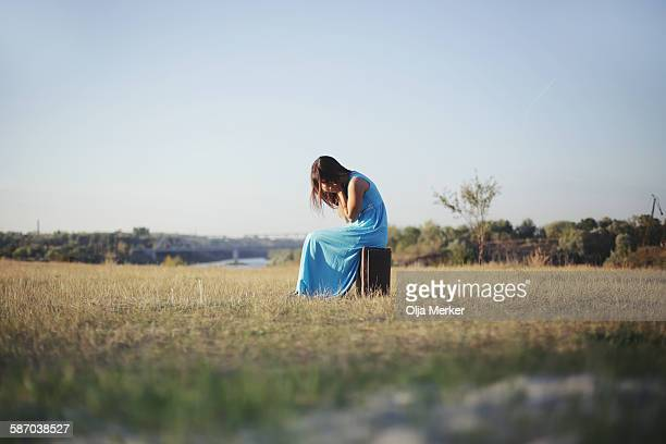young woman sitting on a suitcase in the meadow - long dress stock pictures, royalty-free photos & images