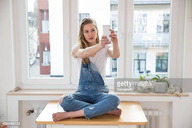 Young woman sitting on a table at home taking selfie with smartphone