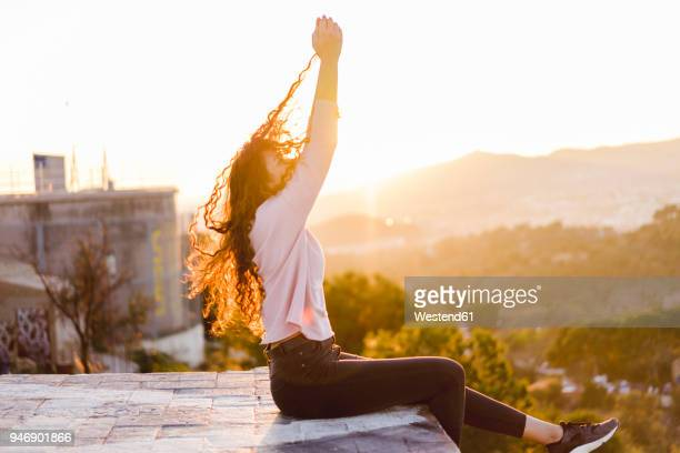 Young woman sitting on a wall at sunset pulling her hair
