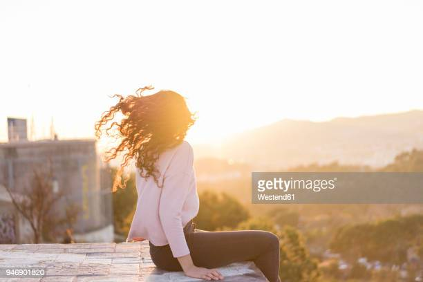 Young woman sitting on a wall at sunset tossing her hair