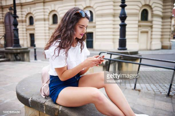 young woman sitting on a wall using cell phone - ホットパンツ ストックフォトと画像