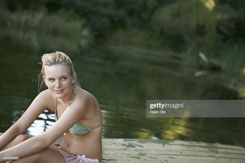 Young Woman Sitting on a Wooden Jetty on a Lake : Stock Photo