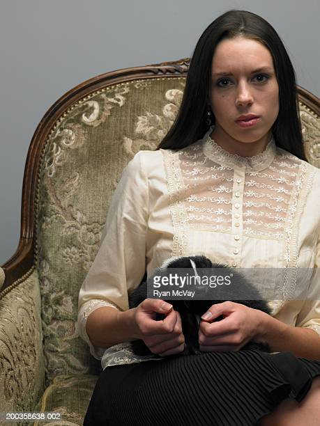 Young woman sitting on armchair, skunk on lap, portrait