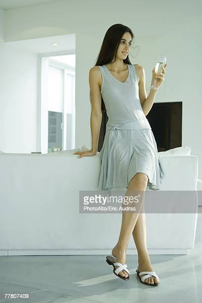 Young woman sitting on back of sofa, holding glass of champagne, full length