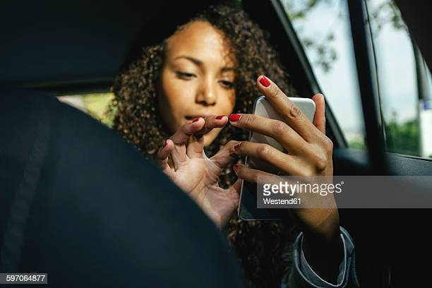 Young woman sitting on back seat of a car using smartphone