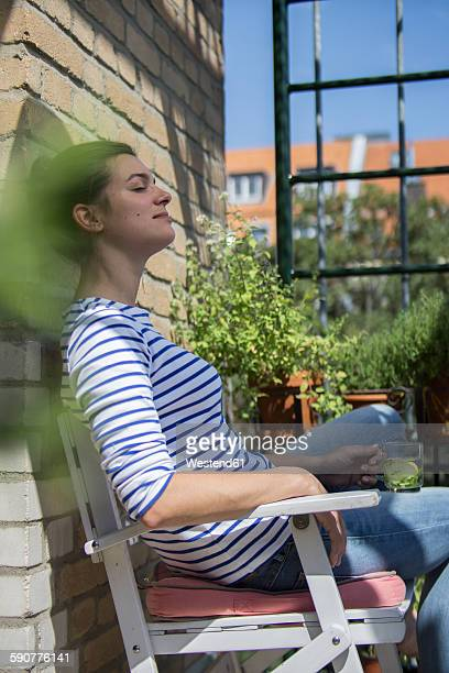 Young woman sitting on balcony, drinking tea, eyes closed