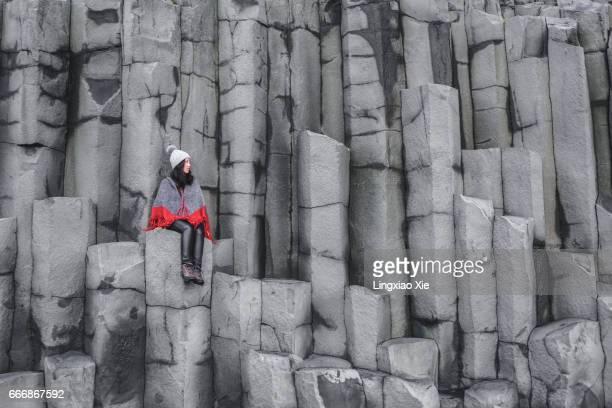 Young woman sitting on Basalt Sea Cliffs, Vik, Iceland