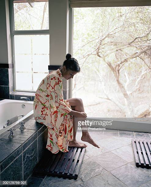 Young woman sitting on bathtub ledge, touching shin, side view