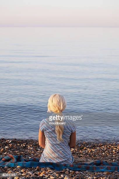 young woman sitting on beach, back view - ponytail stock pictures, royalty-free photos & images