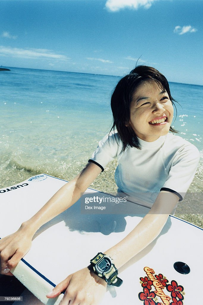 Young woman sitting on beach, holding a paddleboard : Stock Photo