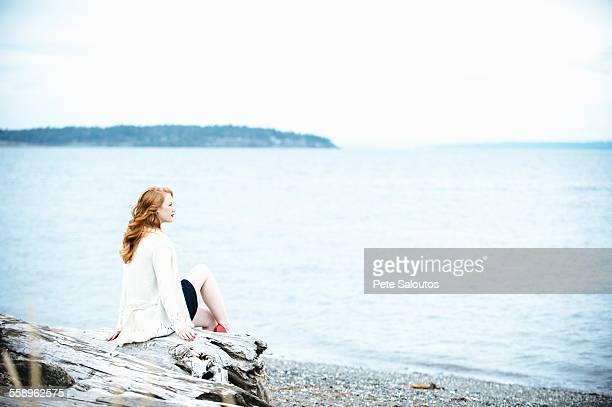 Young woman sitting on beach looking out to sea, Bainbridge Island, Washington State, USA