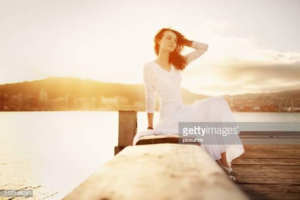 jeune femme assise sur la plage - une seule jeune femme photos et images de collection