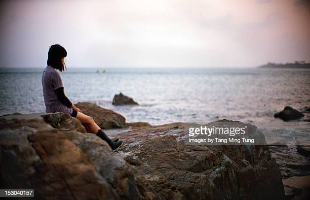 Young woman sitting on beach