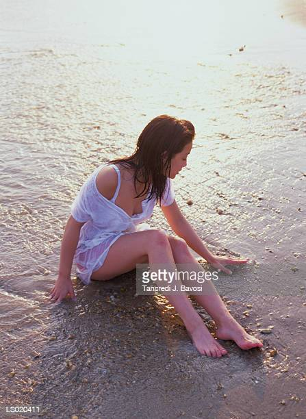 young woman sitting on beach - bavosi stock photos and pictures