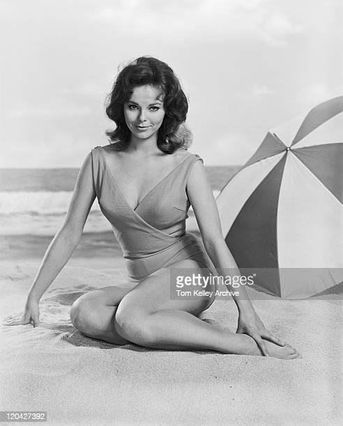 jeune femme assise sur la plage, souriant, portrait - film d'archive photos et images de collection