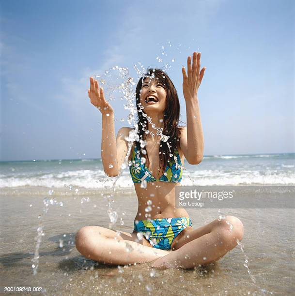 Young woman sitting on beach, splashing in water