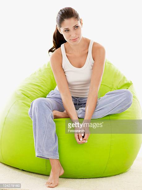 Young woman sitting on beanbag (portrait)