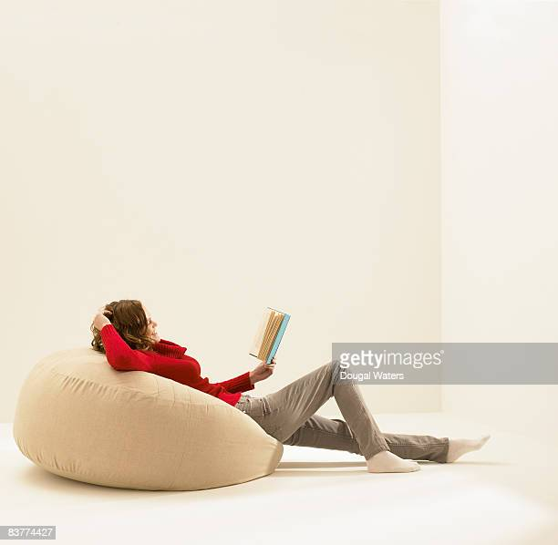 Young woman sitting on beanbag reading book.