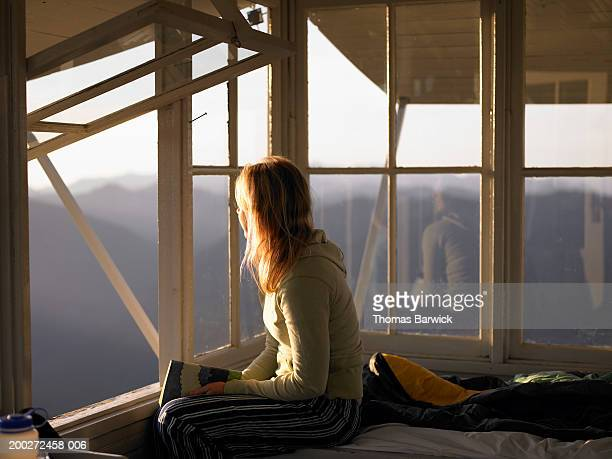 Young woman sitting on bed in mountain cabin, looking out window