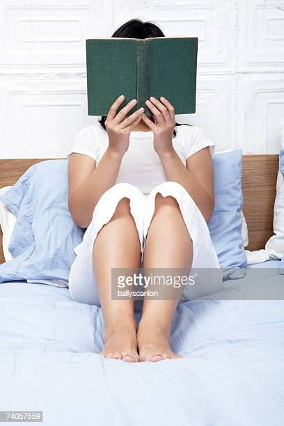 Young woman sitting on bed reading book, face obscured